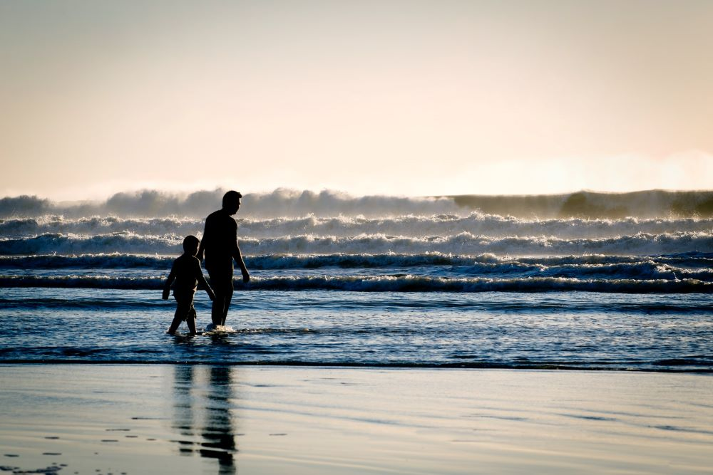 dad and kid walking into the ocean